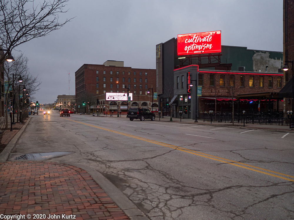 """24 MARCH 2020 - DES MOINES, IOWA: A public service announcement about the coronavirus on an electronic billboard in the historic district of downtown Des Moines. Des Moines was virtually deserted Tuesday as many people chose to stay in their homes. On Tuesday morning, 24 March, Iowa reported over 120 confirmed cases of the Coronavirus (SARS-CoV-2) and COVID-19. Restaurants, bars, movie theaters, places that draw crowds are closed for at least 30 days. The Governor has not ordered """"shelter in place""""  but several Mayors, including the Mayor of Des Moines, have asked residents to stay in their homes for all but the essential needs. People are being encouraged to practice """"social distancing"""" and many businesses are requiring or encouraging employees to telecommute.      PHOTO BY JACK KURTZ"""