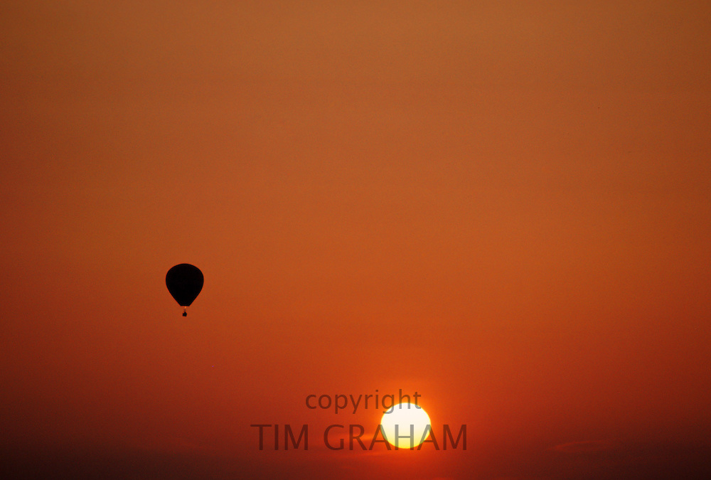 Hot air balloon flying at sunset over Oxfordshire countryside, United Kingdom