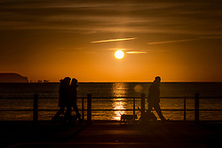 © Licensed to London News Pictures. 01/12/2020. Mudeford, UK. People take a walk on the sea front at Mudeford in Dorset at sunrise. Most of England is experiencing low temperatures and clear skies today on the first day of the Meteorological winter. Photo credit: Peter Macdiarmid/LNP
