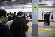 Japanese business commuters patiently waiting for the next train to arrive
