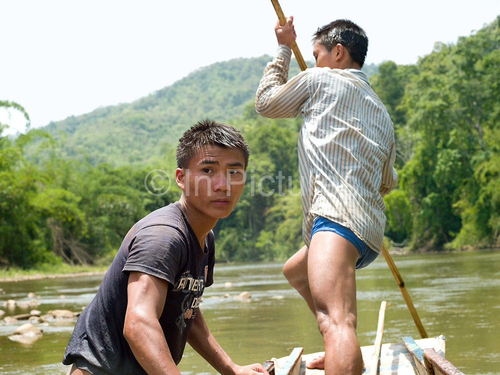 Boatmen Savath and Sengkham navigate their boat up the Nam Ou river using bamboo poles during the dry season when the river level is low, Phongsaly province, Lao PDR. The Nam Ou river connects small riverside villages and provides the rural population with food for fishing. But this river and others like it, that are the lifeline of rural communities and local economies are being blocked, diverted and decimated by dams. The Lao government hopes to transform the country into 'the battery of Southeast Asia' by exporting the power to Thailand and Vietnam.