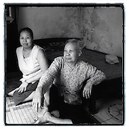 Portrait of a mother and her daughter in their house, close from the railway of Hanoi. They sit on the floor, close from a bed. They look happy and smile