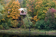 A log house along the Mississippi River surrounded by leaves beginning to turn color for fall - in Almonte, Ontario, Canada.