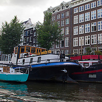 Europe, Netherlands, Amsterdam.  Canal boats and houses of Amsterdam.