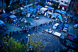 People wait in line to receive charity meal in park, Kamagasaki, Japan.