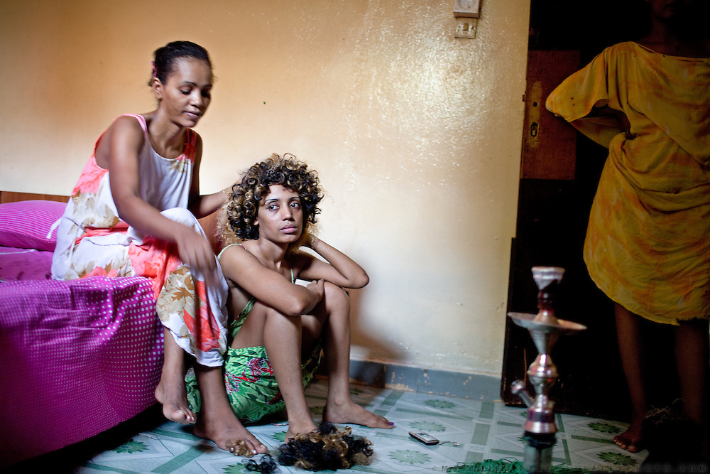 """Muna is combing Tina's hair; the two Ethiopians prostitutes will soon be heading to a club. """"The best is to find an American soldier,"""" says Tina. """"The French are the most generous clients; they pay for our apartments so that we don't have to work. But sooner or later, they all go back to their wives."""" ..One of the communal home of escort girls and prostitutes, in Djibouti. Most of them find their clients in bars and discos. Most of their clients are military people and workers from various nationalities. Prostitute are most of the time high on Khat, a stimulant drug...The geostrategical and geopolitical importance of the Republic of Djibouti, located on the Horn of Africa, by the Red Sea and the Gulf of Aden, and bordered by Eritrea, Ethiopia and Somalia."""