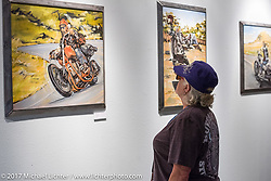 Checking out Kalya Koeune's paintings at the Old Iron - Young Blood exhibition media and industry reception in the Motorcycles as Art gallery at the Buffalo Chip during the annual Sturgis Black Hills Motorcycle Rally. Sturgis, SD. USA. Sunday August 6, 2017. Photography ©2017 Michael Lichter.