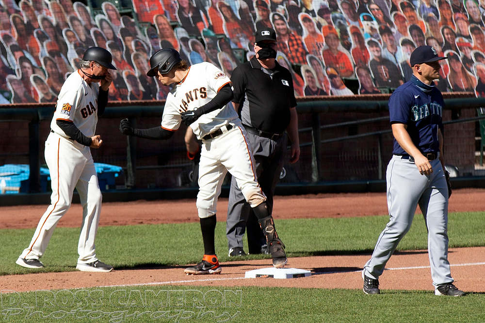 San Francisco Giants first baseman Wilmer Flores, right, gets a congratulatory handshake from third base coach Ron Wotus after hitting a two-RBI triple against the Seattle Mariners during the seventh inning of a Major League Baseball game, Thursday, Sept. 17, 2020 in San Francisco. The Giants defeated the Mariners 6-4. This is a makeup of a postponed game from Wednesday in Seattle. (AP Photo/D. Ross Cameron)
