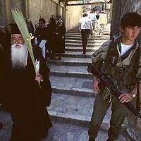 Israel, Jerusalem, Greek Orthodox priest walks past Israeli soldier outside Church of the Holy Sepulcher on Palm Sunday