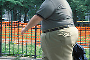An obese man walking with an orange warning fence in the distance