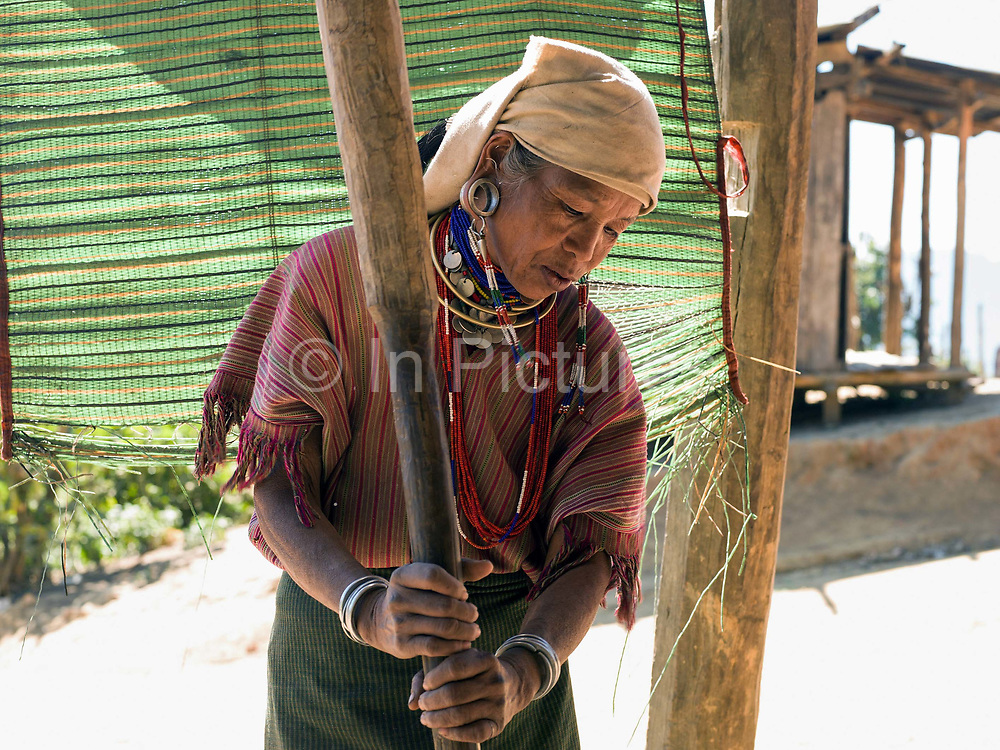 A Kayaw ethnic minority woman processes millet on 19th January 2016 in Kayah State, Myanmar. Wearing traditional costumes made from handwoven cotton, Kayaw women wear many necklaces made from shells, beads and brass coils and fashioned from silver. Distended earlobes are plugged with rings of silver and the ankles and knees encased with brass coils