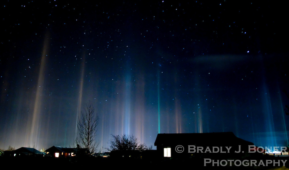 """A phenomenon known as """"light pillars"""" spreads across the night sky over Victor, Idaho. The colorful columns form when light from the ground reflects off flat snow crystals descending through very cold air."""