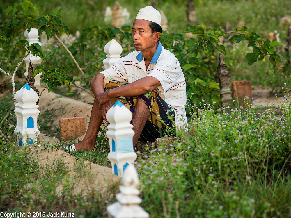 19 JUNE 2015 - PATTANI, PATTANI, THAILAND:  A man prays next to a grave in the Muslim cemetery in Pattani. Perkuboran To'Ayah is the Muslim cemetery in Pattani. It is more than 150 years old. The last Sultan of Pattani, who ruled until Siam (Thailand) annexed Pattani is buried in the cemetery. Many victims of political and sectarian violence that has wracked Thailand's three Muslim majority provinces, Pattani, Narathiwat and Yala are also buried in the cemetery. On Fridays, after morning prayers, Muslim men come to the cemetery to tend to the graves of their family members.  PHOTO BY JACK KURTZ