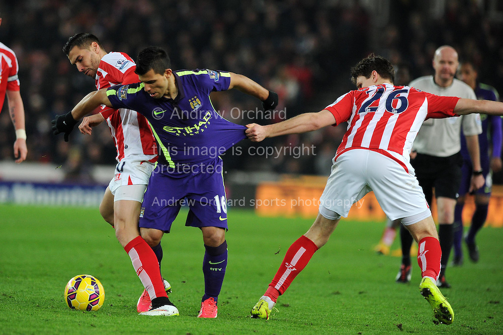 Sergio Aguero of Man city © gets his shirt pulled by Philipp Wollscheid of Stoke city (26). Barclays Premier League match, Stoke city v Manchester city at the Britannia Stadium in Stoke on Trent , Staffs on Wed 11th Feb 2015.<br /> pic by Andrew Orchard, Andrew Orchard sports photography.
