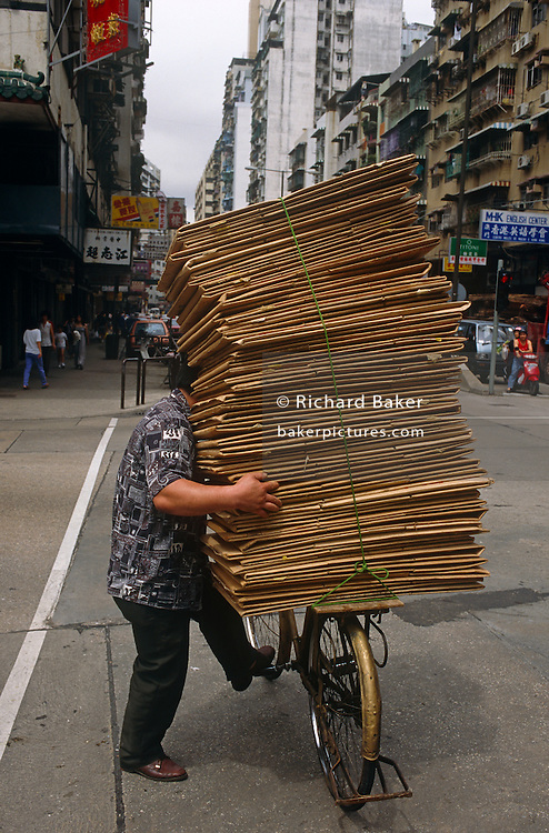 On a street in Macau (also Macao) in the Chinese Special Economic Region (SER), we see the tall stack of cardboard on the back of a bicycle. Its partly-obscured rider and owner has one foot placed on the bike's pedal while his right arm has firm hold of the pile of materials to prevent it from toppling over. In the background we see the signs of many local businesses, their Chinese characters seen clearly on the sides of buildings as pedestrians walk on the pavements. Administered by Portugal until 1999, Macau was the oldest European colony in China, dating back to the 16th century. The administrative power over Macau was transferred to the People's Republic of China (PRC) in 1999, 2 years after Hong Kong's own handover. Macau's name is derived from A-Ma-Gau or Place of A-Ma