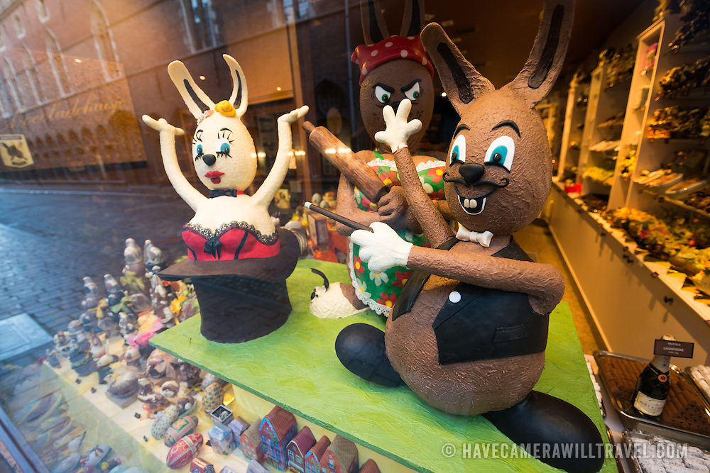 Chocolate Easter Bunnies on display in a chocolate shop window in historic Bruges, Belgium. The region is famous for the quality of its chocolate, and downtown Bruges has many chocolatiers. The cobblestone street is reflected in the window at left of frame.