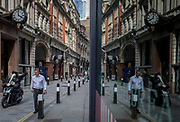 As a courier rides past with an outstretched hand, a businessman walks past Drapers' Hall in Throgmorton Street, City of London, on 11th August, 2017, in London, England.