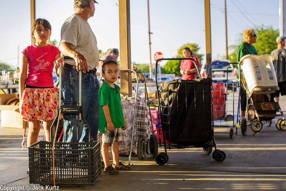 07 AUGUST 2012 - TOLLESON, AZ:   Clients wait for the doors to open at the food bank in Tolleson, AZ, about 15 miles west of Phoenix. The Tolleson food bank has been operating for more than 20 years. It used to serve mostly the families of migrant farm workers that worked the fields around Tolleson but in the early 2000's many of the farms were sold to real estate developers. Now the food bank serves both farm worker families and people who lost their homes in the real estate crash, that his Phoenix suburbs especially hard. More than 150 families a day are helped by the Tolleson food bank, an increase of more than 50% in the last five years.    PHOTO BY JACK KURTZ