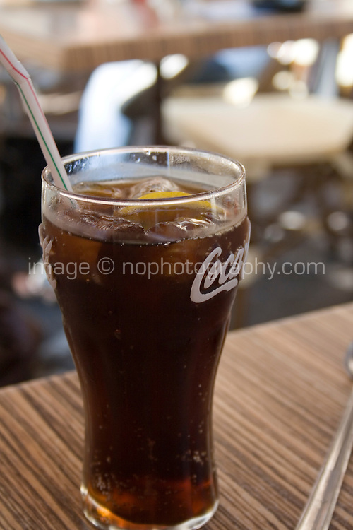 Glass of Coke with ice and lemon on a cafe table