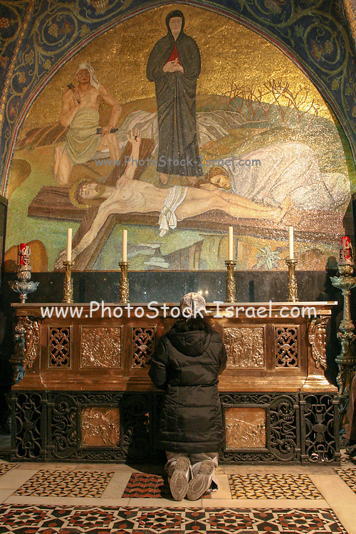 Woman praying in the interior of the Church of the Holy Sepulchre, Jerusalem, Israel
