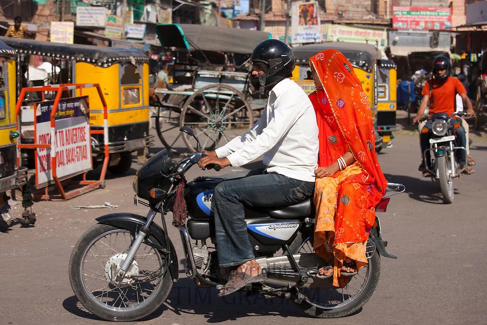 Indian couple riding motorcycle, street scene at Sardar Market at Girdikot, Jodhpur, Rajasthan, Northern India