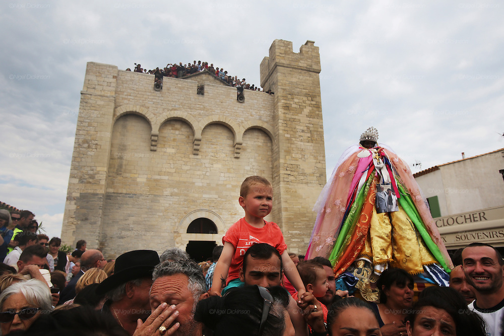 """Roma gypsies carry Saint Sara from the church of Saintes Maries de la Mer on the 24th May<br /><br />""""Le Pelerinage des Gitans""""; the French gypsy pilgrimage of Saintes Maries de la Mer, Camargue, France<br /><br />Sainte Sara is an uncannonized saint, who legend says looked after the Christian Saints Marie Jacobe and Marie Salome, cousins of Mary Magdalene, who arrived, it is said, on the shores of the Camargue in a rudderless boat. Saint Sara is the patron saint of gypsies who come from far and wide to see her. There are even paintings of Sara as 'Kali' the black saint in Eastern Europe. Sara may have been the priestess of 'Ra' the sun-god or even servant girl to the Christian saints. No-one really knows.<br /><br />For a few weeks of the year, Roma, Gitan and Manouche gypsies come from all over Europe in May, camping in caravans around Saintes Maries de la Mer. It is a festive time where they play music, dance, party and christen their children. They all go to see Saint Sara in the crypt, kissing or touching her forehead. Many put robes on her shoulders, making her fat for the procession. In the main Gypsy procession of the 24th May, Saint Sara is allowed to leave her crypt, beneath the church, and is carried from the church to the shores of the mediterranean and back again. One day a year she is free from her prison. Hundred's of years ago the Gypsies used not even to be allowed into the church, only into the crypt like Sara...<br /><br />Roma gypsies still suffer oppressive prejudice and racism and are one of the ethnic groups the most persecuted and marginalised across Europe. The festival is one of the times where they celebrate with people of all races, their faith and traditions"""