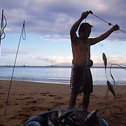Fishing in the traditional style along a Hawaiian beach on the island of Maui.