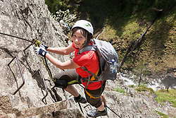 Woman climbing on rock via ferrata towards Lehner Waterfall, Otztal, Tyrol, Austria