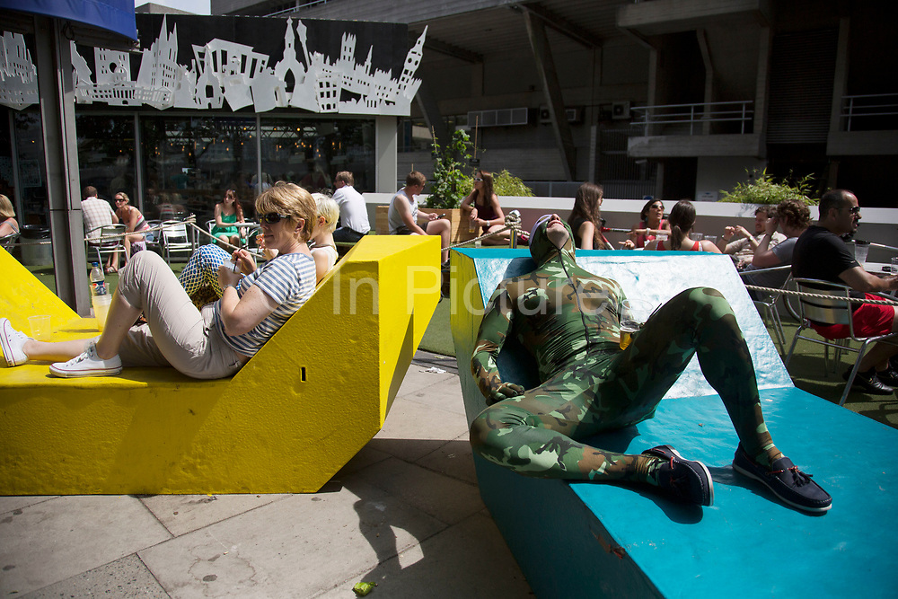 People relaxing on colourful metal benches situated along the South Bank in London, UK. including this man who is on his stag do party and is wearing a camouflage body stocking. Situated outside the National Theatre these structures provide a place for people to lie back and take the weight off their feet while people watching as others walk by. The South Bank is a significant arts and entertainment district, and home to an endless list of activities for Londoners, visitors and tourists alike.