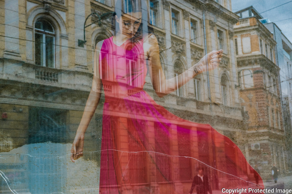 Pedestrians are reflected in the window of a closed dress shop in downtown Sarajevo. Signs of the war are still visible in many of the buildings around Sarajevo.