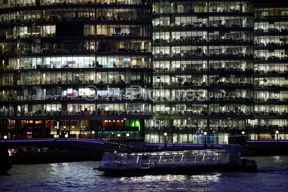 Office buildings at More London lit up at night. This new business district ha glass sided offices which revela the levels of each floor and the business that goes on within each glowing space.