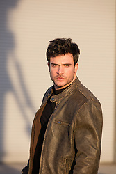 hot man in a leather jacket at sunset