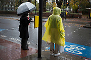 Wet day in Whitechapel in the East End of London, UK. Two different ways to keep the rain off. An umbrella and a yellow see through mac.