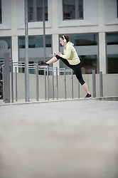 Young woman stretching her leg on railing and listening to music, Bavaria, Germany