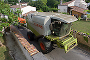 Combine harvester edges slowly through rural hamlet in Langlade, Charente-Maritime region, France.