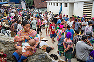 A Hmong woman breast feeding her baby among the crowd of Bac Ha market, Vietnam, Southeast Asia