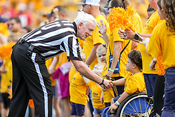 Sep 14, 2019; Morgantown, WV, USA; Umpire James Hyson shakes the hand of a child from WVU Medicine Children's Hospital during a timeout during the second quarter at Mountaineer Field at Milan Puskar Stadium. Mandatory Credit: Ben Queen-USA TODAY Sports