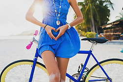March 26, 2016 - Neck down view of young woman with bicycle making heart shape with hands on sandy beach, Krabi, Thailand (Credit Image: © Image Source via ZUMA Press)