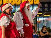 17 SEPTEMBER 2015 - BANGKOK, THAILAND:  Santa Claus and Mrs. Claus, both from Denmark, walk in the World Santa Claus Congress in Bangkok. Twenty-six Santa Clauses from around the world are in Bangkok for the first World Santa Claus Congress. The World Santa Claus Congress has been an annual event in Denmark since 1957. This year's event, hosted by Snow Town, a theme park with a winter and snow theme, hosted the event. There were Santas from Japan, Hong Kong, the US, Canada, Germany, France and Denmark. They presented gifts to Thai children and judged a Santa pageant. Thailand, a Buddhist country, does not celebrate the religious aspects of Christmas, but Thais do celebrate the commercial aspects of the holiday.   PHOTO BY JACK KURTZ