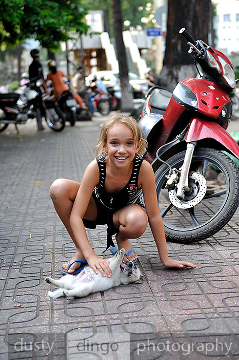 Child (10 years old) playing with small puppy on footpath. Ho Chi Minh City (Saigon), Vietnam