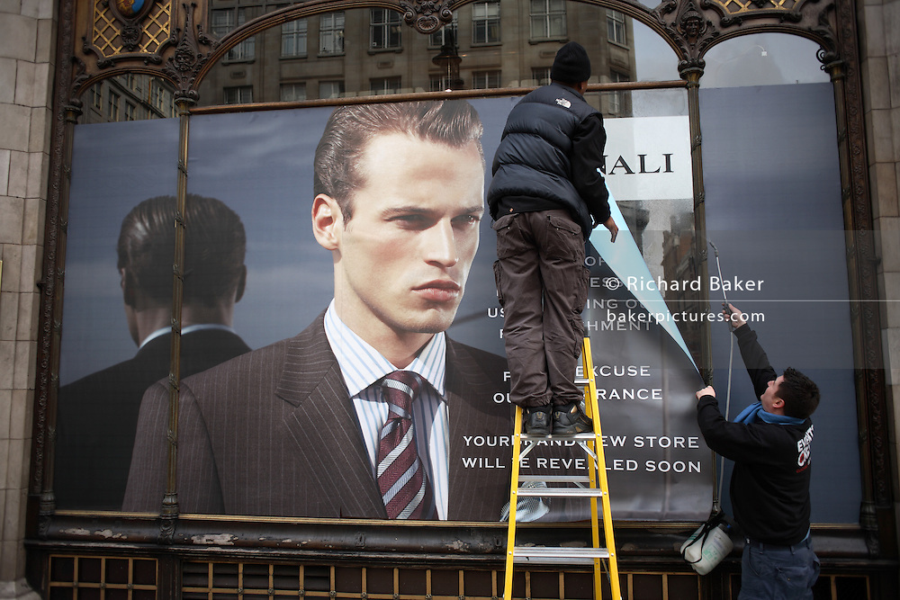 Poster men hang a covering over a window at the Savoy Taylors Guild in The Strand, London UK. Taylors Guild is a high-profile clothing shop next to the famous Savoy Hotel. Part of the Moss Bros Group. Savoy Taylors Guild was pioneering the concept of Gentlemens' taylor a century ago. Its vision in 1903, was ?to supply high grade outfitting for men, in commodious surroundings, giving honest value for cash, and to exercise unceasing efforts in satisfying the wishes of its customers.? The Savoy Taylors Guild shop ? right next to the Savoy Hotel in London?s Strand ? was in itself an immaculate example of the craftsmanship of the times, with elegant brass-fronted windows shining out on the changing and developing world of the Edwardian era.