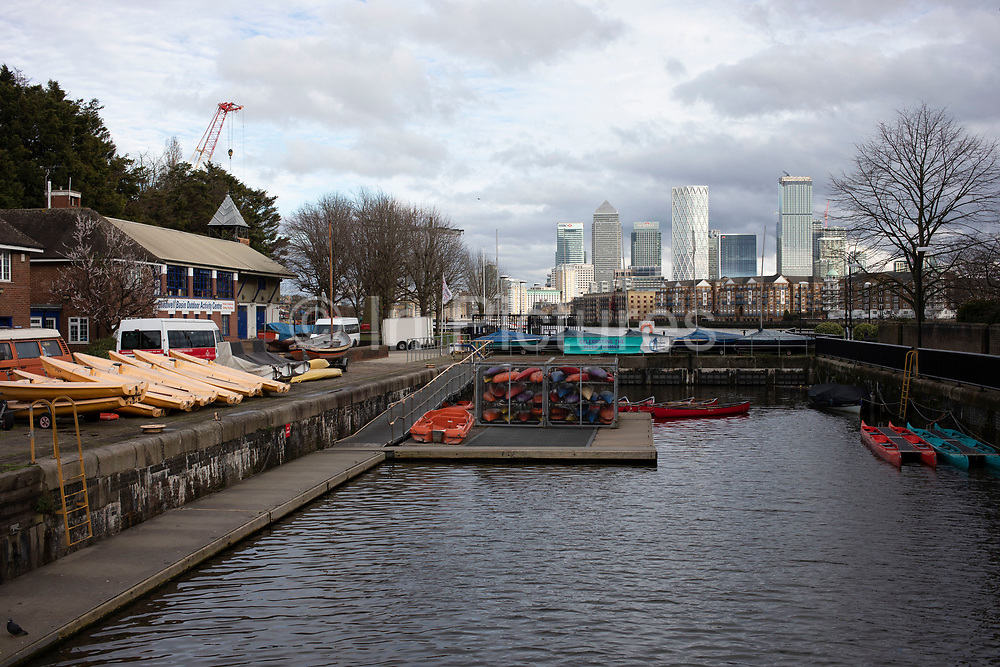 View of the Docklands area, Canary Wharf and financial district across Shadwell Basin Outdoor Activity Centre in Wapping on 23rd February 2020 in London, United Kingdom. Canary Wharf is a financial area which is still growing as construction of new skyscrapers continues. Canary Wharf is London's second home of the British financial sector.
