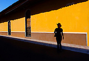 Tourist is silhouetted beside a colorful Spanish colonial house wall, walking the streets of Granada, Nicaragua.