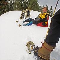 A couple takes a break while snowshoing near Big Sky, Montana.