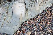 Small beach stones washed up against a smooth outcropping of wave-worn stone.