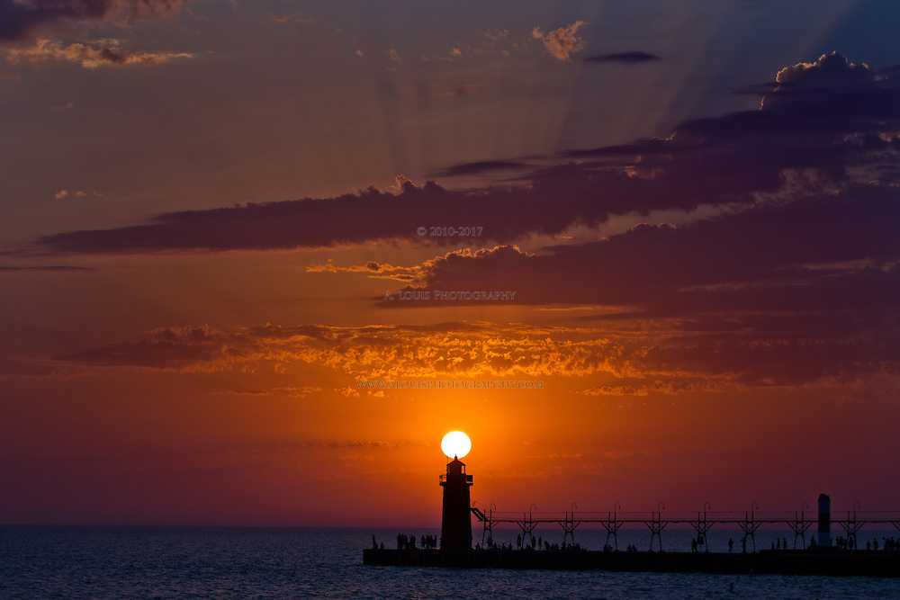 Great sunset over the lighthouse on South Haven's South pier,  With the sun filtering through the clouds creating an awesome ray effect.