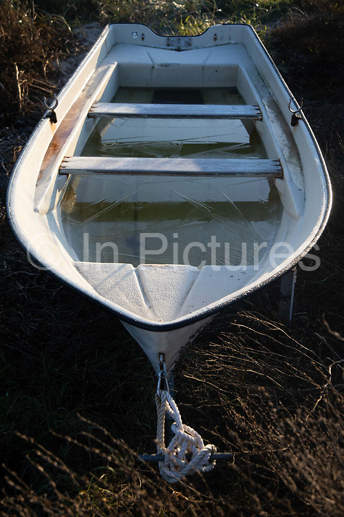 A small boat lying on the beach with ice on the rain water inside, Oct 29th 2019, Skæring, Århus, Denmark. It is autumn and the first morning frost of the year. The beach is in between Århus and Studstrup coal power plant. The sailing and fishing season is almost over at most boats are now pulled high up in the grass by the beach.