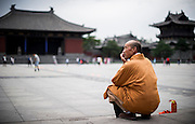 A monk sits on the square of the entrance of the Buddhist Temple of Hua Yan in Datong, China, July 23, 2014.<br /> <br /> Confucianism, Taoism and Buddhism are the three major religions in China. Temples and statues witness their ancient roots all over the Chinese country.<br /> <br /> © Giorgio Perottino