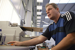 Man with epilepsy working as scanning operator in direct marketing office; using computer mouse,
