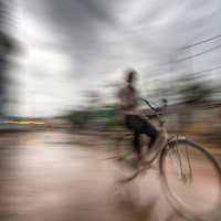 Boy rides bicycle through rainy streets of Siem Riep, Cambodia